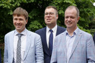 Russian lawyers Ivan Pavlov, right, Vladimir Voronin, center, and Yevgeny Smirnov smile during a break in a court session in front of Moscow Court in Moscow, Russia, Wednesday, June 9, 2021. A Moscow court has outlawed the organizations founded by Russian opposition leader Alexei Navalny by labeling them extremist, the latest move in a campaign to silence dissent and bar Kremlin critics from running for parliament in September. The Moscow City Court's ruling, effective immediately, prevents people associated with Navalny's Foundation for Fighting Corruption and his sprawling regional network from seeking public office. (AP Photo/Alexander Zemlianichenko)
