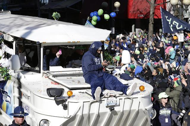 Seattle Seahawks running back Marshawn Lynch rides on the hood of a vehicle during the parade for the NFL football Super Bowl champions, Wednesday, Feb. 5, 2014, in Seattle. The Seahawks defeated the Denver Broncos 43-8 on Sunday. (AP Photo/Ted S. Warren)