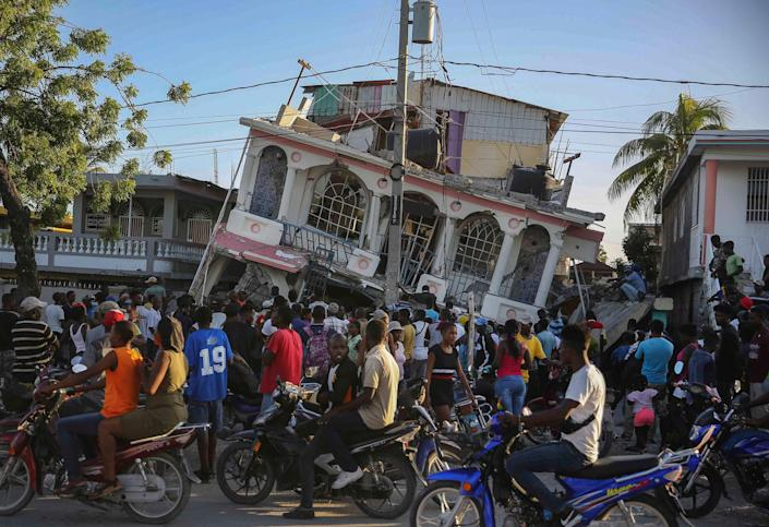 """People gather outside the Petit Pas Hotel, destroyed by the earthquake in Les Cayes, on Aug. 14.<span class=""""copyright"""">Joseph Odelyn—AP</span>"""
