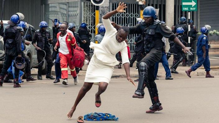 An anti-riot police man in Zimbabwe tackles a woman with his boot as they dispersed a crowd gathered to hear an address by leader of the MDC (Movement for Democratic Change) Alliance, Nelson Chamisa at Morgan Tsvangirai House, the party headquarters, in Harare, on November 20, 2019