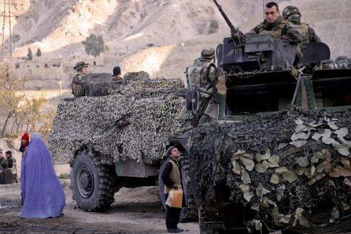 A file photo, taken in 2008, shows an Afghan woman (L) holding her child as a boy looks up at French soldiers as they patrol in the village of Surobi, some 60km east of Kabul. The French president's office on Saturday confirmed that four French soldiers were killed and five were wounded in an attack claimed by the Taliban in Afghanistan's eastern Kapisa province