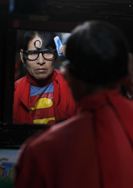 In this photo taken June 14, 2012, Avelino Chavez, wearing his signature Superman costume, combs his hair at his home in Lima, Peru. Chavez, 52, took on the Superman persona 15 years ago, when he lost his job as a security guard, and says he has had work ever since. Chavez also says he only earns about $160 US dollars per month, but that he has the strength of a superhero. (AP Photo/Martin Mejia)