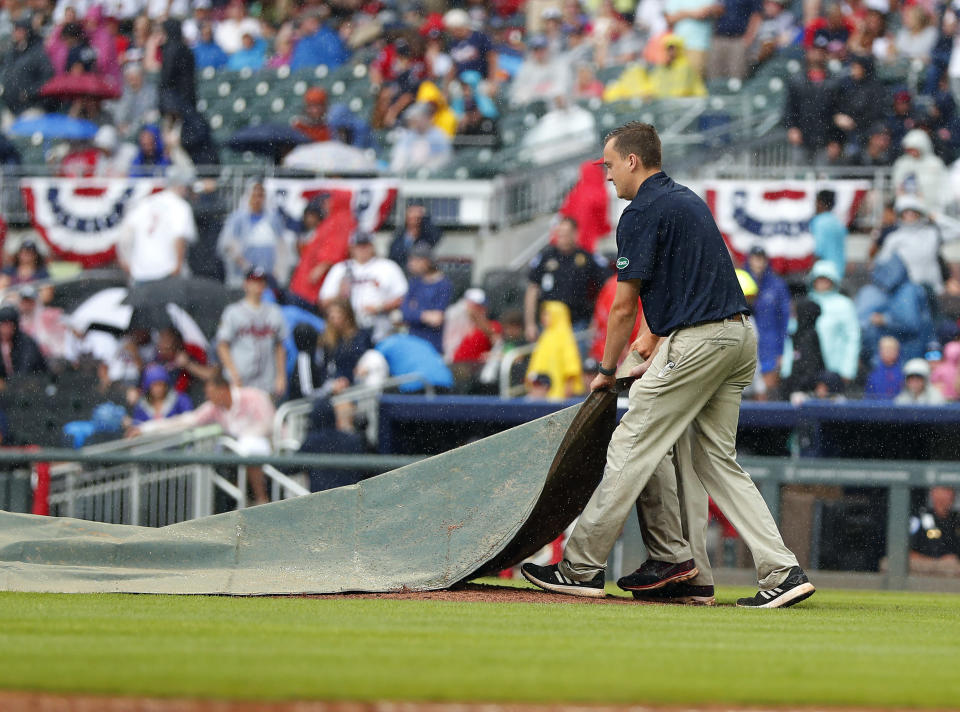 Members of the Atlanta Braves grounds crew rush to cover the infield during a rain shower during the sixth inning of the first game of a baseball doubleheader against the New York Mets. Monday, May 28, 2018, in Atlanta. (AP Photo/John Bazemore)