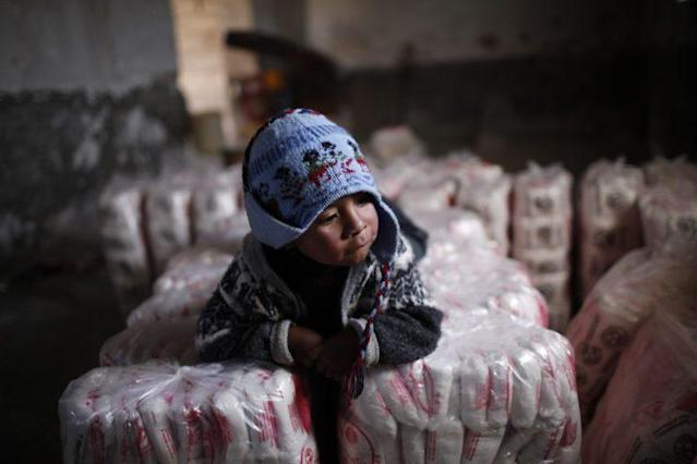 In this 2010 photo, the child of a salt miner rests on bags of salt from the Uyuni salt desert. (Photo: Dado Galdieri/AP)
