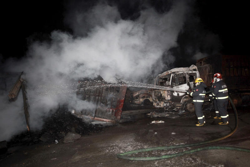In this photo released by Xinhua News Agency, firefighters try to extinguish burning vehicles in the aftermath of an explosion at a plant operated by the Hebei Shenghua Chemical Industry Co. Ltd Wednesday, Nov. 28, 2018 in Zhangjiakou city, northeastern China's Hebei province. The explosion early Wednesday outside the chemical plant in northeastern China has killed people and destroyed scores of vehicles. (Xinhua via AP)