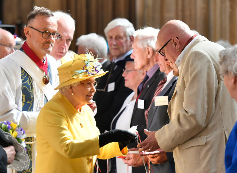 Britain's Queen Elizabeth II distributes the Maundy money during the Royal Maundy Service at St George's Chapel in Windsor, west of London on April 18, 2019. - Maundy Thursday is the Christian holy day falling on the Thursday before Easter. The Queen commemorates Maundy by offering 'alms' to senior citizens - retired pensioners recommended by clergy and ministers of all denominations, in recognition of service to the Church and to the local Community. Each recipient receives two purses, one red and one white. (Photo by ARTHUR EDWARDS / POOL / AFP) (Photo credit should read ARTHUR EDWARDS/AFP via Getty Images)