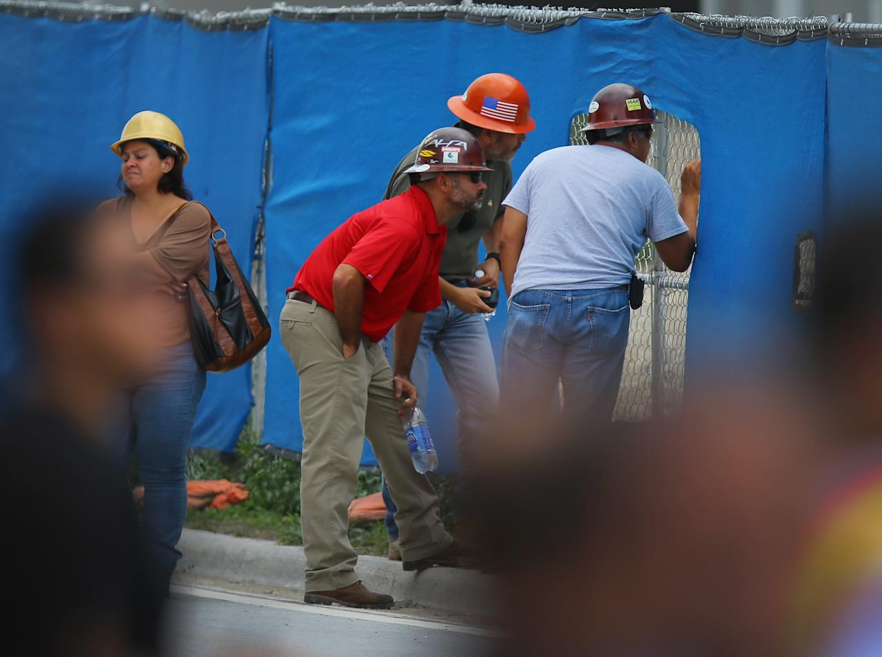 DORAL, FL - OCTOBER 10: Construction workers watch as search and rescue people look for possible survivors in the rubble of a four-story parking garage that was under construction and collapsed at the Miami Dade College's West Campus on October 10, 2012 in Doral, Florida.  Early reports indicate that one person was killed, at least seven people injured and an unknown number of people may be buried in the rubble.  (Photo by Joe Raedle/Getty Images)