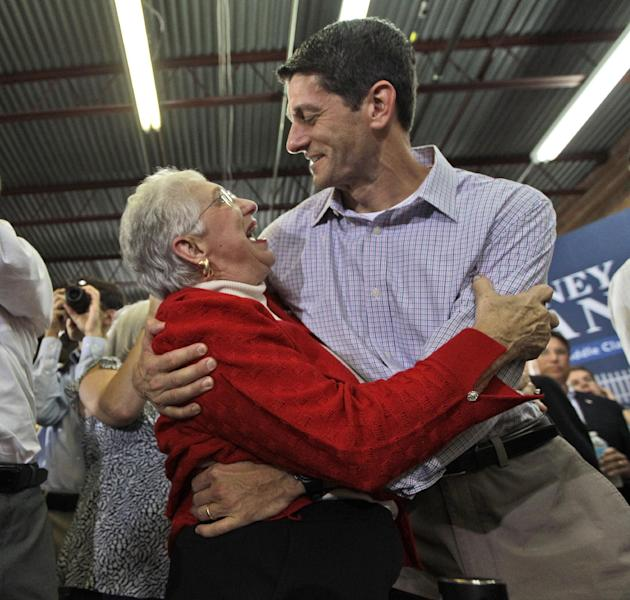 FILE - This Aug. 12, 2012 file photo shows an enthusiastic supporter hugging Republican vice presidential candidate, Rep. Paul Ryan, R-Wis., at a campaign event in High Point, N.C. Obama goes airborne in a doozie of a bear hug with a pizza guy in Florida. Joe Biden cozies up with a biker chick in Ohio. Even the more reserved Mitt Romney seems to be loosening up some with people he meets on the campaign trail. Kissing babies and slapping backs are so yesterday. The 2012 candidates are putting their all into the campaign cliche of pressing the flesh. (AP Photo/Mary Altaffer, File)