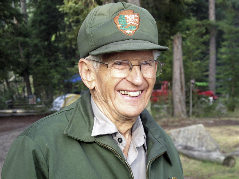 This Sept. 6, 2013 photo shows Lyle Ruterbories smiling as he speaks with a visitor to the Kintla Lake Campground in Glacier National Park, Mont. Ruterbories is the National Park Service's oldest ranger at age 93. He and his wife Marge managed the campground since 1991, and Ruterbories has continued on his own since her death in 2005. (AP Photo/Matt Volz)