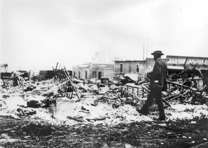 An African-American man with a camera looking at the skeletons of iron beds which rise above the ashes of a burned-out block after the Tulsa Race Massacre, Tulsa, Oklahoma, June 1921. (Photo by Oklahoma Historical Society/Getty Images)