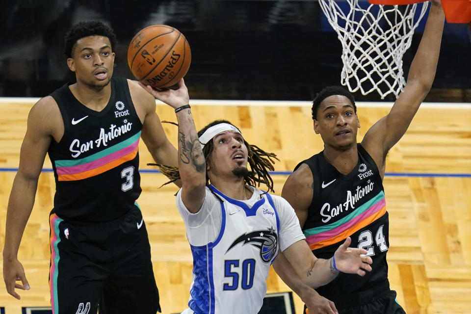 Orlando Magic guard Cole Anthony (50) takes a shot as he gets between San Antonio Spurs forward Keldon Johnson (3) and guard Devin Vassell (24) during the first half of an NBA basketball game, Monday, April 12, 2021, in Orlando, Fla. (AP Photo/John Raoux)