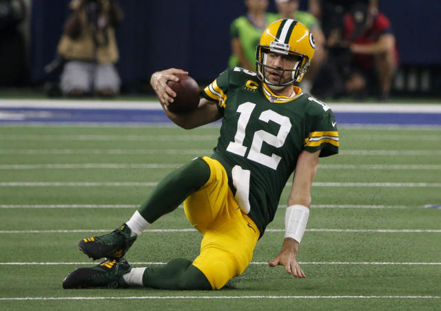 Green Bay Packers quarterback Aaron Rodgers slides to the ground after running the ball during the second half of the team's NFL football game against the Dallas Cowboys in Arlington, Texas, Sunday, Oct. 6, 2019. (AP Photo/Michael Ainsworth)