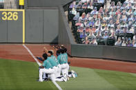 Seattle Mariners players kneel along the left field line with fists in the air as they watch a video tribute after the playing of the national anthem before the Mariners home opener baseball game against the Oakland Athletics Friday, July 31, 2020, in Seattle. (AP Photo/Elaine Thompson)