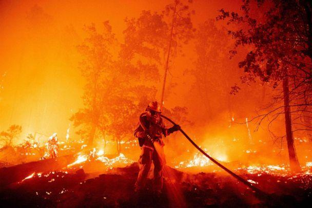 PHOTO: In this Sept. 7, 2020, file photo, a firefighter douses flames as they push towards homes during the Creek fire in the Cascadel Woods area of Madera County, Calif. (Josh Edelson/AFP via Getty Images, FILE)