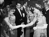 <p>Actress Julie Christie wore white elbow length gloves that matched the monarch's when they met in 1966. Christie paired hers with a sleeveless floral dress at the premiere of <em>Born Free</em>.</p>