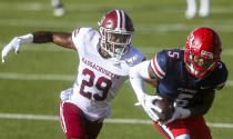 Liberty wide receiver DJ Stubbs (5) hauls in a pass as he is defended by Massachusetts player Cody Jones (29) during the first half of an NCAA college football game on Friday, Nov. 27, 2020, at Williams Stadium in Lynchburg, Va. (AP Photo/Shaban Athuman)