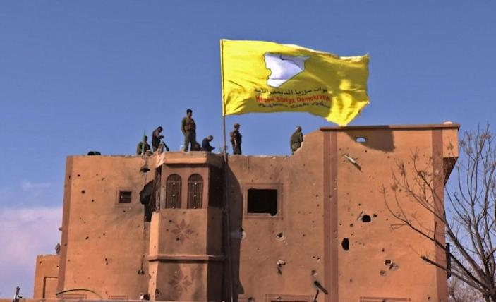 "US-backed fighters of the Syrian Democratic Forces raise their flag in the Islamic State group's last redoubt of Baghouz as their commanders proclaim the total elimination of its ""caliphate"" (AFP Photo/Handout)"
