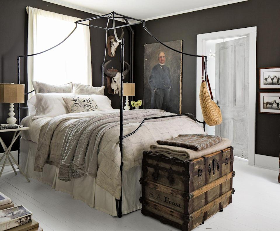 """<p>A dark wall color creates a cozy cocoon of a bedroom, but steer clear of that dark dungeon feel by pairing charcoal or black with liberal doses of white. Here, white painted floors, pale lamps, and white and linen toned bedding provide a welcome contrast to the sleeping quarters' warm black-brown surroundings. </p><p><strong>Get the Look:</strong><br>Wall Paint Color: <a href=""""https://m.valsparpaint.com/color-chip.php"""" rel=""""nofollow noopener"""" target=""""_blank"""" data-ylk=""""slk:Fired Earth by Valspar"""" class=""""link rapid-noclick-resp"""">Fired Earth by Valspar</a> </p>"""
