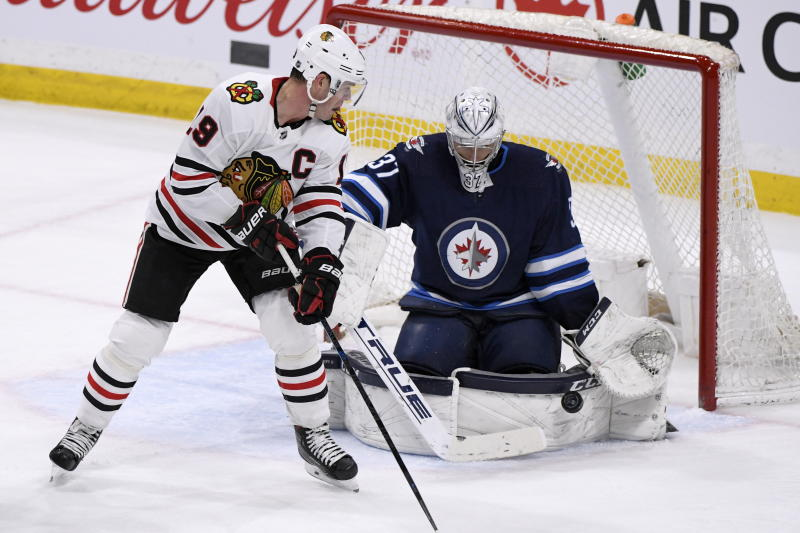 Winnipeg Jets goaltender Connor Hellebuyck (37) makes a save on Chicago Blackhawks' Jonathan Toews (19) during the third period of an NHL hockey game Sunday, Feb. 16, 2020, in Winnipeg, Manitoba. (Fred Greenslade/The Canadian Press via AP)