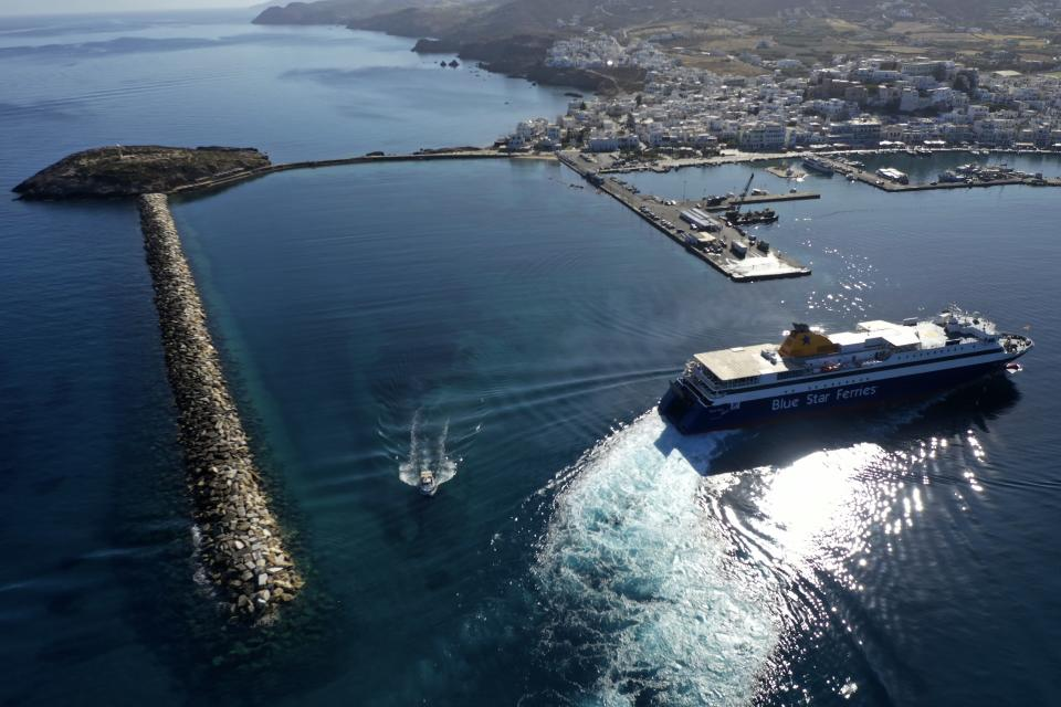 A ferry approaches the port on the Aegean island of Naxos, Greece, Friday, May 14, 2021. Greece launched its tourism season Friday amid a competitive scramble across the Mediterranean to lure vacationers emerging from lockdowns. (AP Photo/Thanassis Stavrakis)