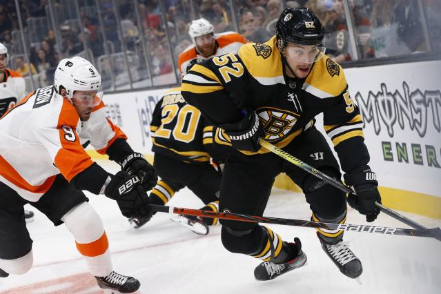 Philadelphia Flyers' Ivan Provorov (9) defends against Boston Bruins' Sean Kuraly (52) during the first period of an NHL hockey game in Boston, Sunday, Nov. 10, 2019. (AP Photo/Michael Dwyer)