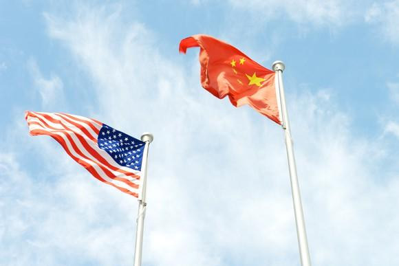 American and Chinese flags on poles.