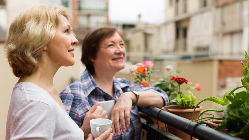 Smiling aged female friends relaxing with cup of coffee on balcony.