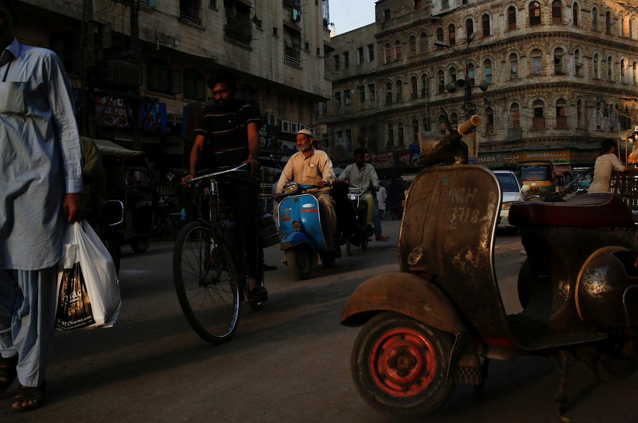 <p>A man rides a Vespa scooter on a busy street, in a low-income neighbourhood in Karachi, Pakistan on March 6, 2018. (Photo: Akhtar Soomro/Reuters) </p>