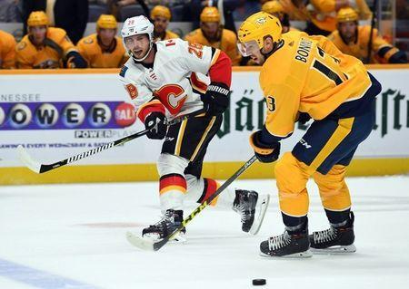 Oct 9, 2018; Nashville, TN, USA; Calgary Flames center Elias Lindholm (28) passes the puck past Nashville Predators center Nick Bonino (13) during the first period at Bridgestone Arena. Mandatory Credit: Christopher Hanewinckel-USA TODAY Sports