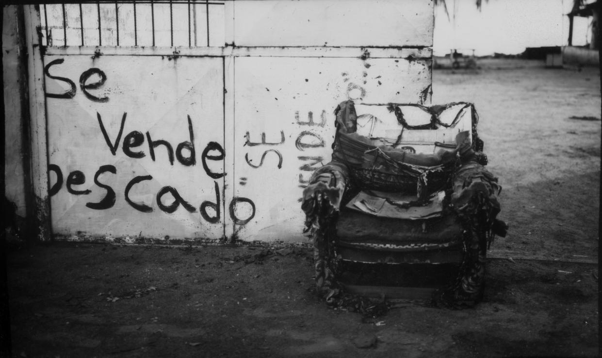 "A damaged chair outside a fisherman's home marked with words that read in Spanish ""Fish for sale"" in Cabimas, Venezuela, near oil-contaminated Lake Maracaibo. (Photo: Rodrigo Abd/AP)"
