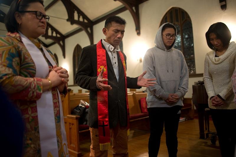 Harry Pangemanan praying with fellow congregants