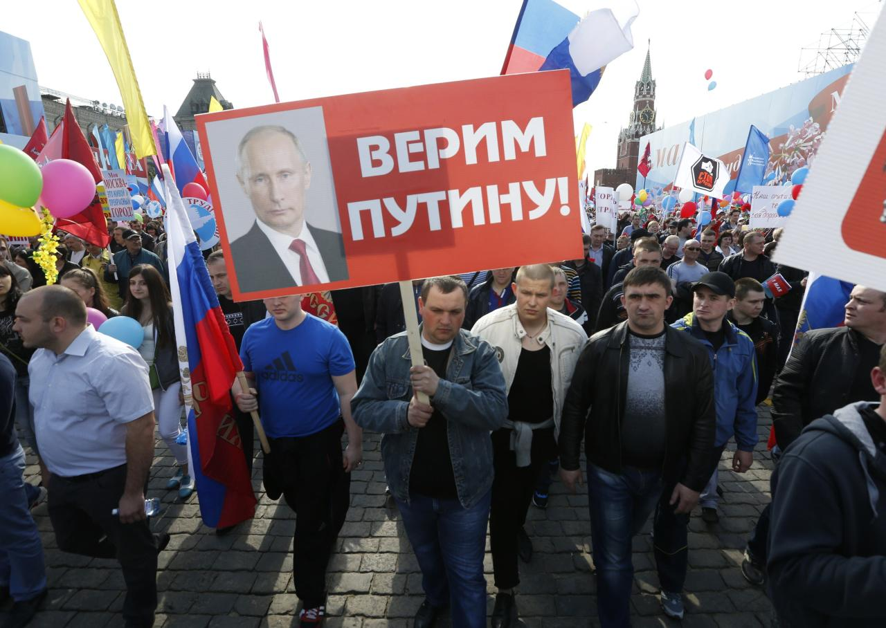 """People walk through Red Square with flags and banners during a rally in Moscow May 1, 2014. Russians celebrate the coming of Spring and since communist times, also Labour Day on the first day of May. The placard reads, """"We believe in Putin."""" REUTERS/Sergei Karpukhin (RUSSIA - Tags: BUSINESS EMPLOYMENT SOCIETY)"""