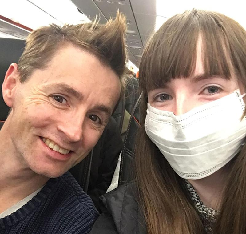 Courtney Ward, 25, and her partner Anthony Burns on board a plane. Ms Ward has a face mask on.