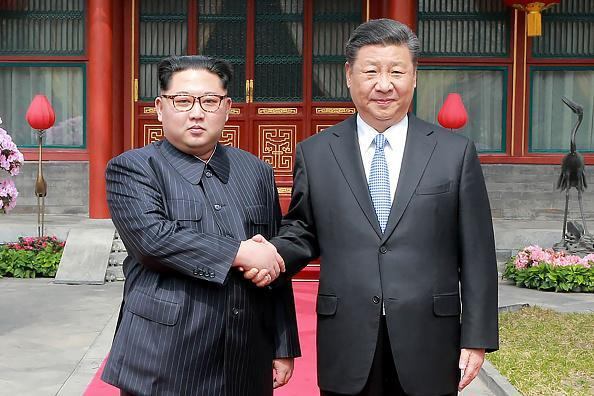 China's President Xi Jinping (R) shaking hands with North Korean leader Kim Jong Un in Beijing. Kim was treated to a lavish welcome by the Chinese president during a secretive trip to Beijing as both sides seek to repair frayed ties ahead of landmark summits with Seoul and Washington. (Photo credit: AFP/Getty Images)