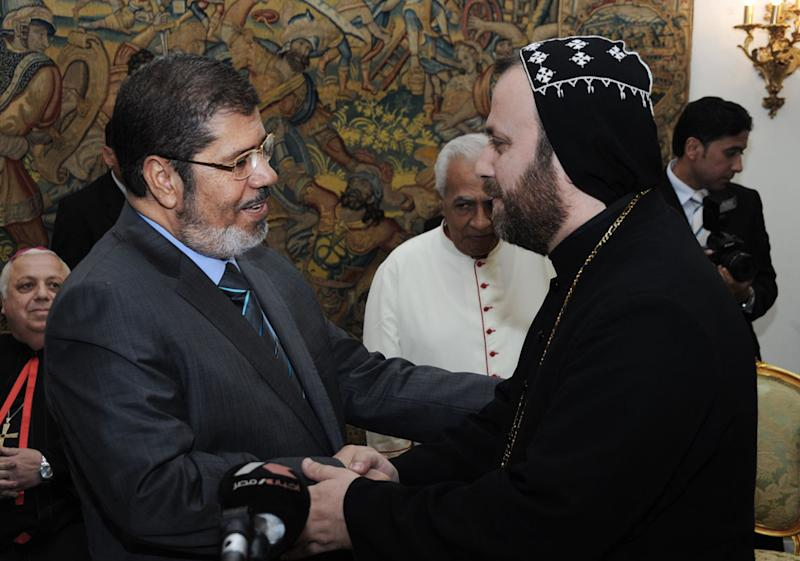 In this photo released by Middle East News Agency, the Egyptian official news agency, President-elect Mohammed Morsi, left, shakes hands with a Christian leader, name not given, in Cairo, Egypt, Monday, June 27, 2012. Now that Egypt has its first freely elected civilian president, the still-dominant military may be seeking to emulate the Turkish model a mostly Muslim nation with a history of military rule and democratic evolution. (AP Photo/Mohammed Abd El-Maaty, Middle East News Agency, HO)