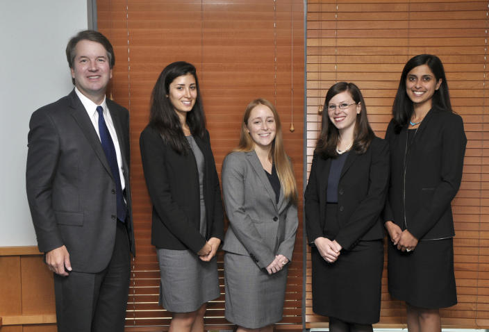 In this image provided by the Department of Justice, Judge Brett Kavanaugh poses for a photo with his law clerks in 2014–2015, in Washington. It was the first all-women law clerk class in the history of the D.C. Circuit. Kavanaugh has been a conservative team player, and the Supreme Court nominee has stepped up to make a play at key moments in politics, government and the law dating to the Bill Clinton era. (Department of Justice via AP)
