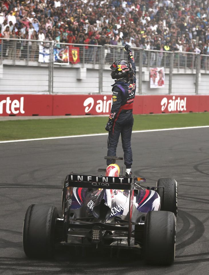 Red Bull Formula One driver Sebastian Vettel of Germany celebrates atop his car after winning the Indian F1 Grand Prix at the Buddh International Circuit in Greater Noida, on the outskirts of New Delhi, October 27, 2013. REUTERS/Adnan Abidi (INDIA - Tags: SPORT MOTORSPORT F1)