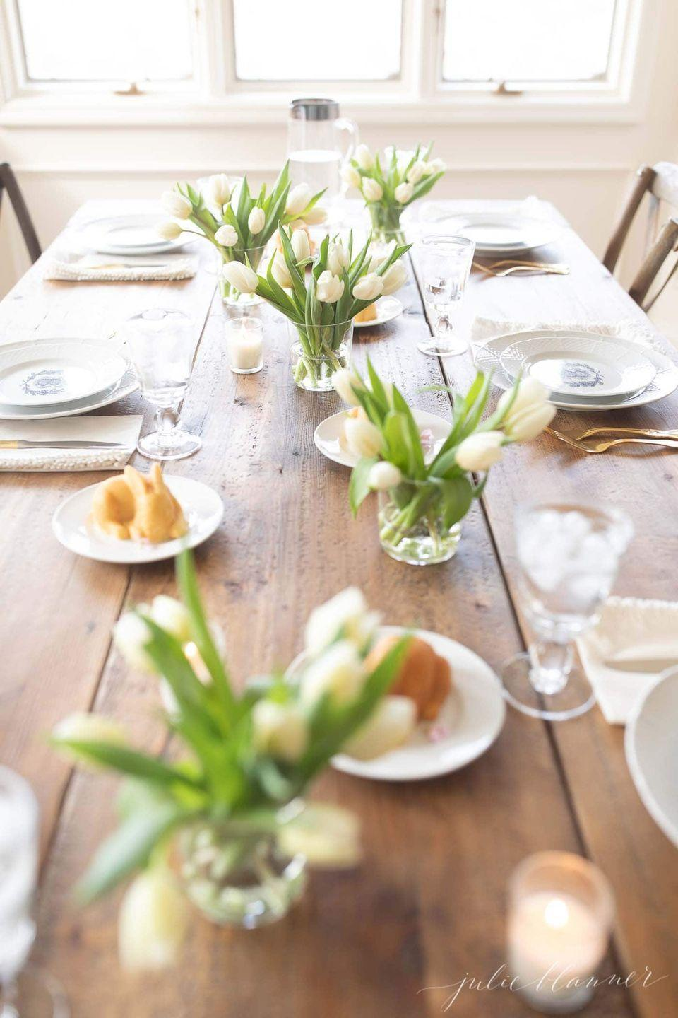 """<p>White tulips and glassware paired with gold silverware makes for a welcoming Easter tablescape. Don't forget the <a href=""""https://www.goodhousekeeping.com/food-recipes/dessert/a38185/raspberry-lemon-pound-cake-recipe/"""" rel=""""nofollow noopener"""" target=""""_blank"""" data-ylk=""""slk:pound cake"""" class=""""link rapid-noclick-resp"""">pound cake</a> bunnies as a finishing touch. <br><br><a class=""""link rapid-noclick-resp"""" href=""""https://www.amazon.com/Nordic-Ware-Baby-Bunny-Cakes/dp/B00UKB4B9U?tag=syn-yahoo-20&ascsubtag=%5Bartid%7C10055.g.2217%5Bsrc%7Cyahoo-us"""" rel=""""nofollow noopener"""" target=""""_blank"""" data-ylk=""""slk:SHOP BUNNY BAKING PANS"""">SHOP BUNNY BAKING PANS</a><br><em><a href=""""https://julieblanner.com/tulip-centerpiece/"""" rel=""""nofollow noopener"""" target=""""_blank"""" data-ylk=""""slk:Get the tutorial at Julie Blanner »"""" class=""""link rapid-noclick-resp""""><br>Get the tutorial at Julie Blanner »</a> <br></em></p>"""
