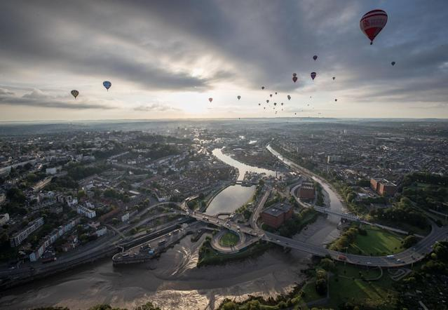 <p>Hot air balloons take to the skies as they participate in the mass assent at sunrise on the second day of the Bristol International Balloon Fiesta on August 11, 2017 in Bristol, England. (Photo: Matt Cardy/Getty Images) </p>