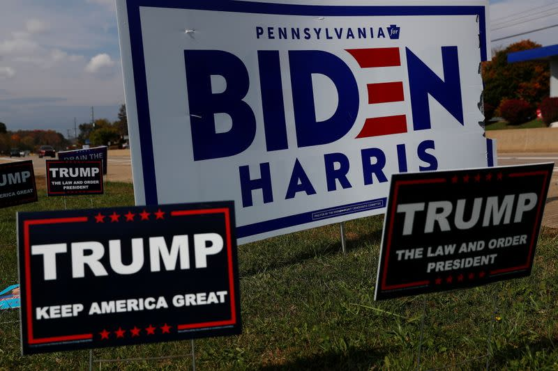 Campaign signs for U.S. Democratic presidential candidate Joe Biden and Vice presidential candidate Kamala Harris stand with signs for U.S. President Donald Trump on a hillside in Monroeville, Pennsylvania