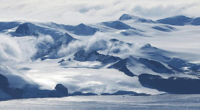 <p>Mountains stand near the coast of West Antarctica as seen from a window of a NASA Operation IceBridge airplane on October 27, 2016 in-flight over Antarctica. (Photo: Mario Tama/Getty Images) </p>