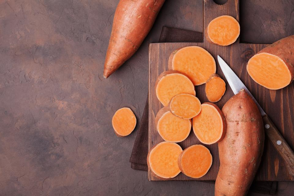 Raw sweet potatoes on wooden kitchen board top view. Organic food. Copy space for text or design.