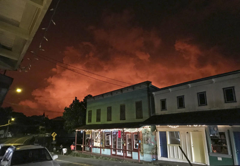 In this Monday, July 16, 2018 photo provided by Nathan Kam, a glow from the eruption of the Kilauea volcano is seen over Pahoa, Hawaii. The small, rural town of Pahoa is the gateway to the eruption pouring rivers of lava out of Hawaii's Kilauea volcano. But ironically it's nearly impossible for residents and visitors on the ground to see the lava - a fact that's squeezing the tourism-dependent local economy. (Nathan Kam via AP)