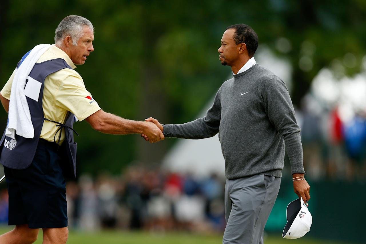 ARDMORE, PA - JUNE 14: (L-R) Caddie Steve Williams and Tiger Woods of the United States shake hands on the 18th green during a continuation of Round One of the 113th U.S. Open at Merion Golf Club on June 14, 2013 in Ardmore, Pennsylvania. (Photo by Scott Halleran/Getty Images)