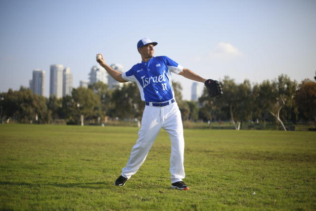 In this Tuesday, Jan. 14, 2020 photo, Danny Valencia throws a ball during Israel's national baseball team practice, in Tel Aviv, Israel. As a baseball-crazed kid growing up in Miami, Valencia dreamed of playing in the Major Leagues. The thought of heading to the Olympics, for a foreign country no less, never crossed his mind. But that's the next surreal step for the 35-year-old Valencia, who recently became an Israeli citizen thanks to his Jewishness and is now the star player in Team Israel's improbable run to the Tokyo Games. (AP Photo/Ariel Schalit)