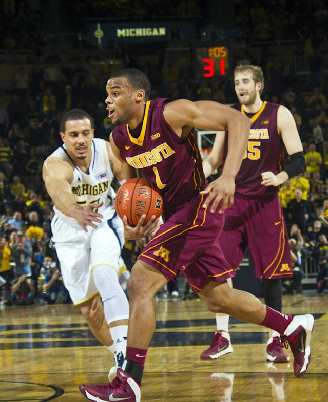 Minnesota guard Andre Hollins (1) goes to the basket as Michigan forward Jordan Morgan defends during the second half of an NCAA college basketball game at Crisler Center in Ann Arbor, Mich., Saturday, March 1, 2014. Michigan won 66-56. (AP Photo/Tony Ding)