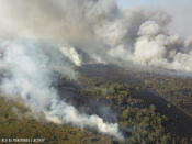 In this undated photo provided by the Association of Forest Communities of Peten on June 2020, fire and smoke envelop a part of the Laguna Del Tigre National Park in northern Guatemala. In 2020, the region has experienced a worrisome uptick in fires set illegally to clear land, while government resources to control flames have been diverted to manage the COVID-19 pandemic. (Alvaro Ba/ACOFOP via AP)