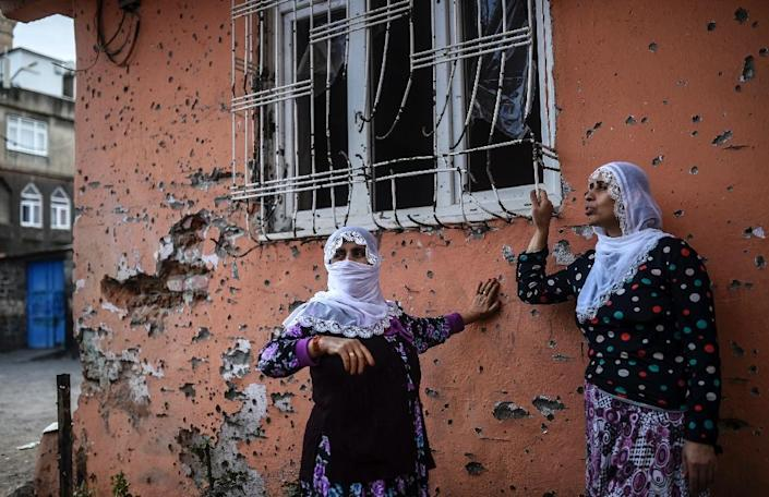 Women stand in front of a bullet-riddled wall that was damaged during clashes between Turkish troops and Kurdish militants in the district of Sur in Diyarbakir, southeastern Turkey, on October 31, 2015 (AFP Photo/Bulent Kilic)