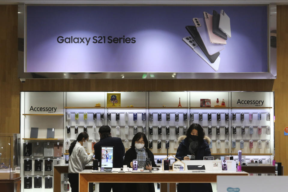 Visitors try out Samsung Electronics' Galaxy Z Folder2 5G smartphones at its shop in Seoul, South Korea, Thursday, Jan. 28, 2021. Samsung Electronics Co. said Thursday its operating profit for last quarter rose by more than 26% as it capped off a robust business year where its dual strength in parts and finished products allowed it to thrive amid the pandemic. (AP Photo/Ahn Young-joon)