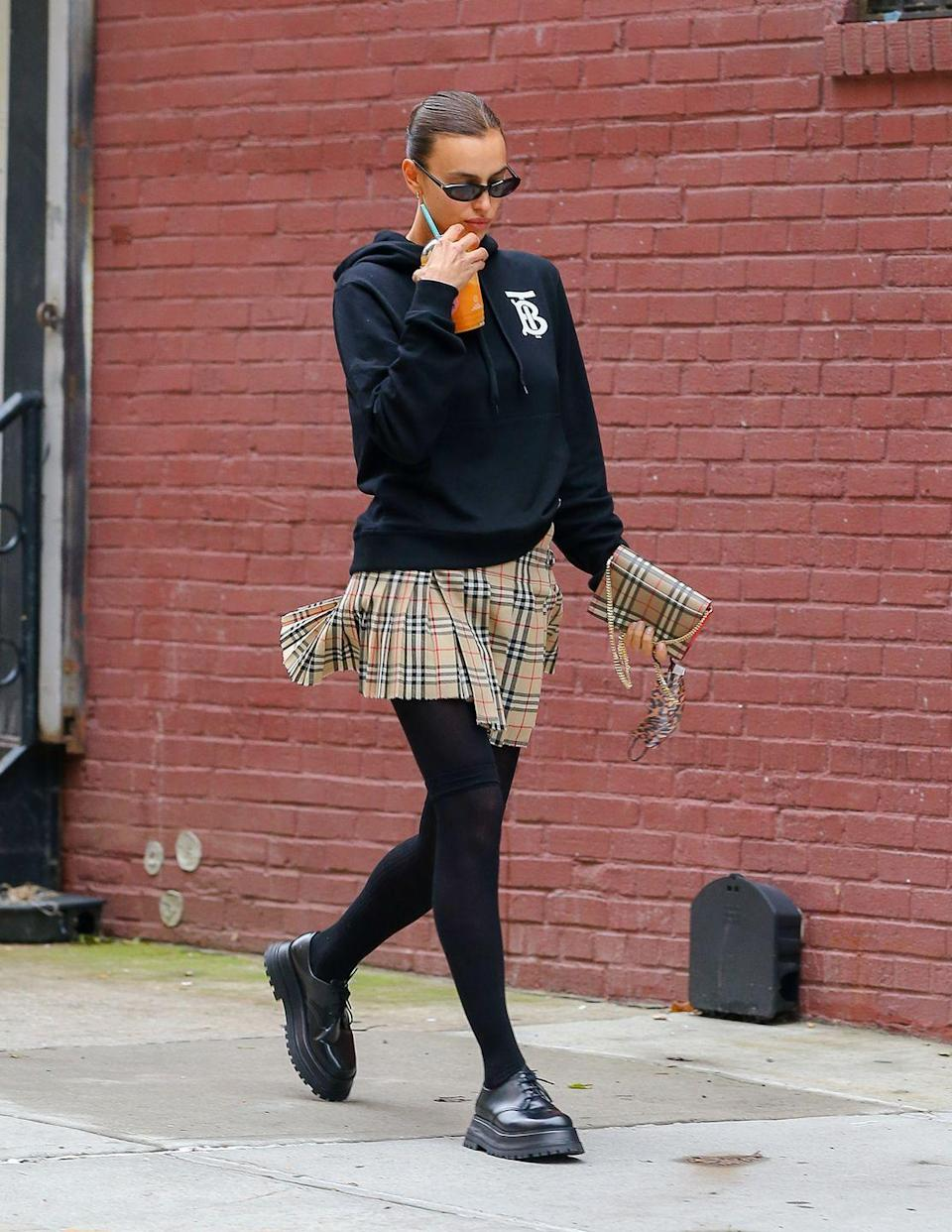 """<p>Irina Shayk wore head-to-toe Burberry to <a href=""""https://www.dailymail.co.uk/tvshowbiz/article-8839255/Irina-Shayk-keeps-low-profile-black-Burberry-hoodie-pleated-skirt.html"""" rel=""""nofollow noopener"""" target=""""_blank"""" data-ylk=""""slk:pick up"""" class=""""link rapid-noclick-resp"""">pick up</a> her and ex-husband Bradley Cooper's daughter, Lea De Seine, in New York.</p><p>The 34-year-old model paired her Burberry hoodie, with black lace-ups, a checked kilt and <a href=""""https://go.redirectingat.com?id=127X1599956&url=https%3A%2F%2Fwww.farfetch.com%2Fuk%2Fshopping%2Fwomen%2Fburberry-check-print-mini-bag-item-14696049.aspx&sref=https%3A%2F%2Fwww.elle.com%2Fuk%2Ffashion%2Fcelebrity-style%2Fg34359706%2Firina-shayk-style-file%2F"""" rel=""""nofollow noopener"""" target=""""_blank"""" data-ylk=""""slk:matching bag"""" class=""""link rapid-noclick-resp"""">matching bag</a> for the perfect back-to-school look.</p><p>This isn't the first time Shayk has repped the Nova-check so whole-heartedly, having previously <a href=""""https://www.elle.com/uk/fashion/a28080681/irina-shayk-lea-de-seine-shayk-cooper-matching-burberry/"""" rel=""""nofollow noopener"""" target=""""_blank"""" data-ylk=""""slk:twinned with daughter De Seine"""" class=""""link rapid-noclick-resp"""">twinned with daughter De Seine</a> in matching heritage check dresses from the British brand. </p><p><a class=""""link rapid-noclick-resp"""" href=""""https://go.redirectingat.com?id=127X1599956&url=https%3A%2F%2Fwww.farfetch.com%2Fuk%2Fshopping%2Fwomen%2Fburberry-vintage-check-mini-kilt-item-14603409.aspx&sref=https%3A%2F%2Fwww.elle.com%2Fuk%2Ffashion%2Fcelebrity-style%2Fg34359706%2Firina-shayk-style-file%2F"""" rel=""""nofollow noopener"""" target=""""_blank"""" data-ylk=""""slk:SHOP IRINA'S BURBERRY KILT NOW"""">SHOP IRINA'S BURBERRY KILT NOW</a></p><p><a class=""""link rapid-noclick-resp"""" href=""""https://go.redirectingat.com?id=127X1599956&url=https%3A%2F%2Fwww.farfetch.com%2Fuk%2Fshopping%2Fwomen%2Fburberry-lace-up-derby-shoes-item-14727234.aspx&sref=https%3A%2F%2Fwww.elle.com%2Fuk%2Ffashion%2Fcelebrity-style%2F"""